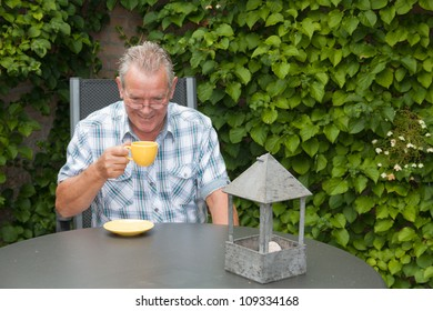 Retired senior Dutch man with a smile on his face whilst drinking a cup of hot coffee in his back yard
