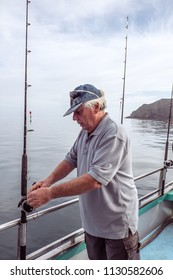 Retired senior male adult tourist on a fishing charter boat looking at rod, at Mangonui, Far North District, Northland, New Zealand, NZ