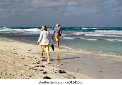 Retired senior people walking on the white sand of a beach in Varadero, Cuba. Photo taken - January 1, 2000 -