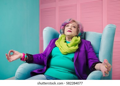 Retired woman enjoy life and relaxing in blue armchair, meditating and dreaming.