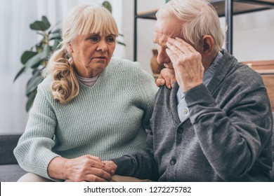 retired woman holding hands with senior husband having headache