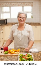 Retired woman looking at the camera in the kitchen