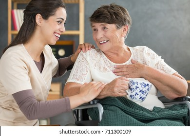 Retired woman in wheelchair talking to happy nurse and drinking tea from a white mug with floral pattern