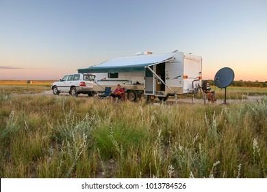 Retiree sitting under awning of caravan with four wheel drive vehicle at sunset.