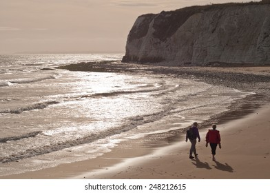 Retirement: a couple walking on a beach in Kent, England, in evening light.
