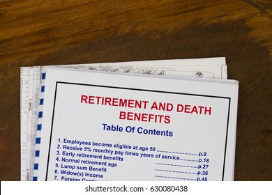 Retirement and death benefits  training manual with blueprints in a wood texture background.