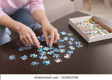 Retirement entertainment. Senior woman playing jigsaw puzzle at home, empty space