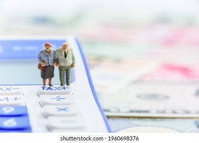 Retirement fund, pension income tax and social security benefit concept : Older american couple stands near a tax button on a calculator, depicts a single largest expense in retirement e.g pension tax