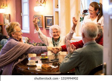 Retirement home occupants sitting at the table together and playing various games