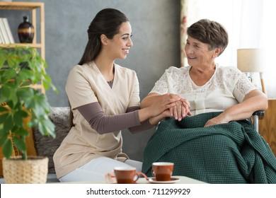 Retirement home volunteer holding elder woman's hand in gesture of support before rehabilitation
