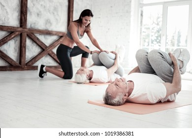 Retirement is not the end. Selective focus on a focused mature man training in a gym and exercising during a group workout session.