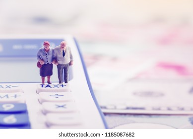 Retirement / pension income tax and social security benefit concept : Older american couple stands near a tax button on a calculator, depicts a single largest expense in retirement e.g pension tax