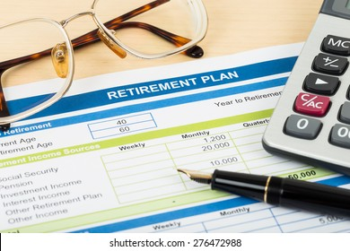 Retirement plan with glasses, pen, and calculator; document is mock-up