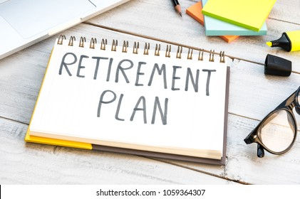Retirement plan hand written in a note, concept of starting senior investment pension retirement life with pen and eyeglasses on white wooden background.