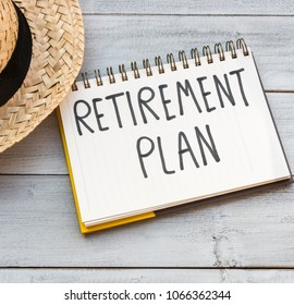 Retirement plan hand written in a note, concept of starting senior investment pension retirement life with hat on white wooden background. Happy vacation retire.