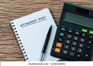 Retirement planning concept, calculator with empty notepad with pen and handwriting underline headline as Retirement Plan on wood table, plan of saving and investment for expense after retire life.