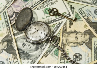 Retirement Planning concept - pocket watch with a key  on money background