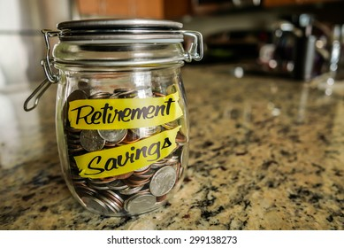 """Retirement Savings Money Jar. A clear glass jar filed with coins and bills, saving money. The words """"Retirement Savings"""" written on the outside."""