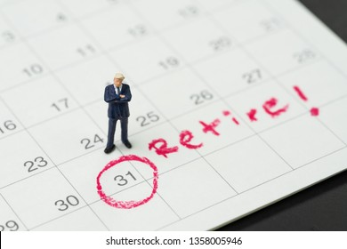 Retirement target or planning to quit job or financial freedom, miniature people businessman standing and thinking about date with important target red circle on calendar with text Retire.