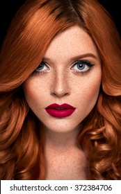 Retouched studio beauty portrait of a redhead caucasian girl with curly hair, bright make up and freckles on dark background