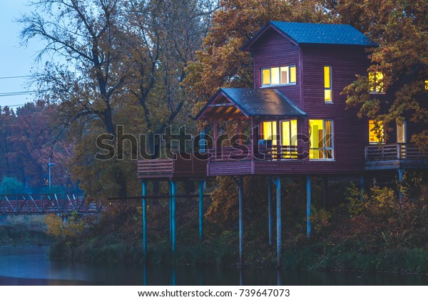 Retreat near lake in the evening. Wooden cottages on piles in oak forest. House with panoramic windows and lights on. Vacation getaway.