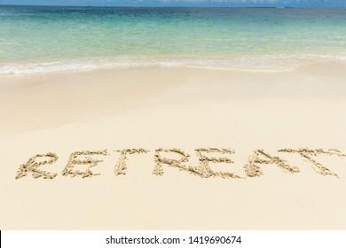 Retreat Text Written On Sand Near The Idyllic Sea At Beach