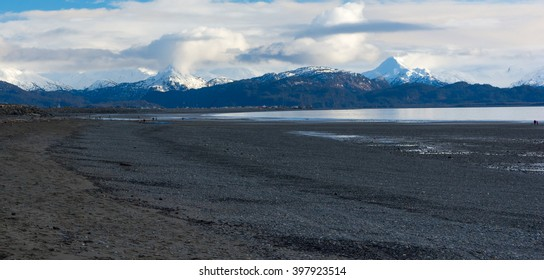 A retreating tide leaves a gravel beach bare.