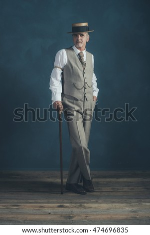54056614071 Retro 1920s dandy in suit standing with cane in front of gray wall.
