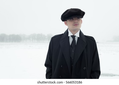 Retro 1920s english gangster with black coat and flat cap standing in winter snow landscape. Peaky blinders style.