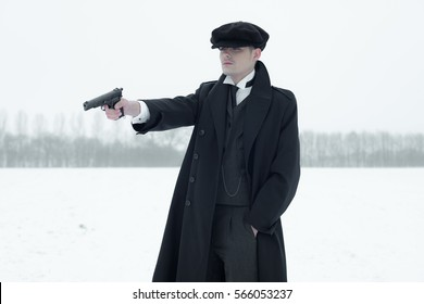 Retro 1920s english gangster with black coat and flat cap shooting with gun in winter snow landscape. Peaky blinders style.