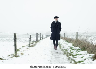Retro 1920s english gangster with black coat and flat cap walking in winter snow landscape. Peaky blinders style.