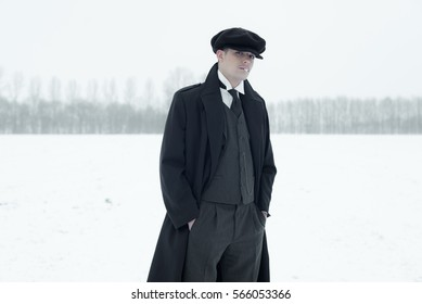 Retro 1920s english gangster with black coat and flat cap smoking cigarette in winter snow landscape. Peaky blinders style.
