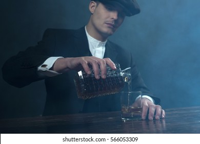 Retro 1920s english gangster with flat cap pouring whiskey. Peaky blinders style.