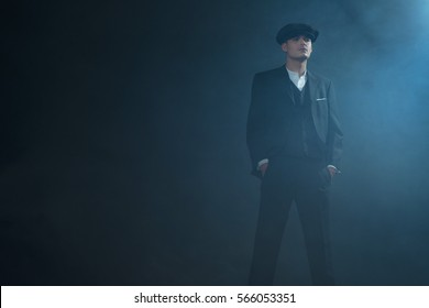 Retro 1920s english gangster wearing suit and flat cap standing in smoky room. Peaky blinders style.