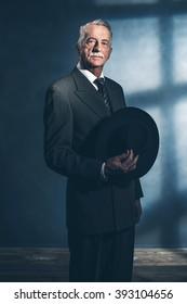 Retro 1940 senior businessman holding hat standing in room.