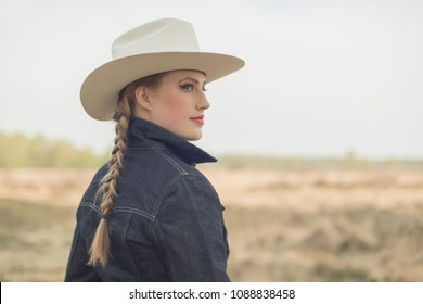 Retro 1950s cowgirl in jeans jacket in countryside.