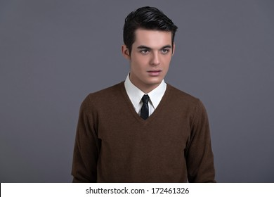 Retro 1950s fashion man with dark grease hair. Wearing brown sweater with black tie. Studio shot against grey.