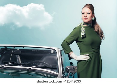 Retro 1960s woman in green dress standing next sportscar.