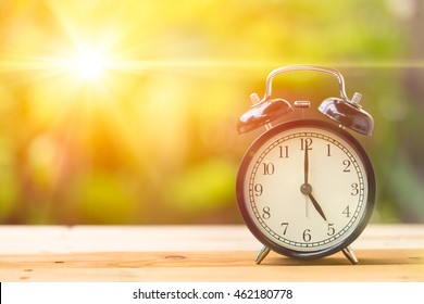 Retro 5 o'clock and Morning sun with Bright and Flare Day Light Blur Green Garden Background with space for text.