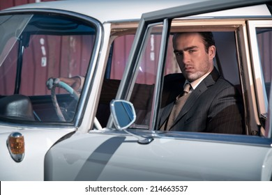 Retro 60s fashion business man wearing grey suit with tie sitting in classic car.