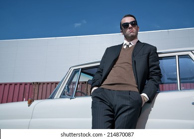 Retro 60s fashion business man wearing grey suit and black sunglasses standing against classic car.
