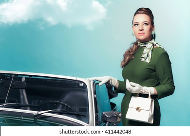 Retro 60s woman in green dress standing next convertible car.