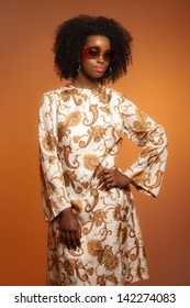 Retro 70s Fashion African Woman With Paisley Dress And Sunglasses Brown Background