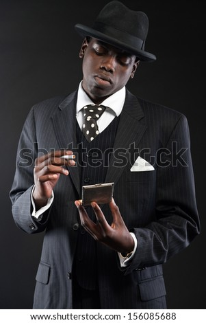 Retro african american gangster man wearing striped suit and tie and black  hat. Taking cigarette c5aeb58e09ee