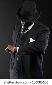 Retro african american gangster wearing striped suit and tie and black hat. Looking on his watch. Studio shot.