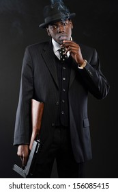 Retro african american mafia man wearing striped suit and tie and black hat. Smoking cigar. Holding a gun. Studio shot.