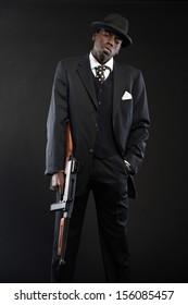 Retro african american mafia man wearing striped suit and tie and black hat. Holding machine gun. Studio shot.
