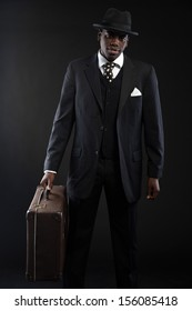 Retro african american traveller wearing striped suit and tie and black hat. Holding big suitcase. Studio shot.