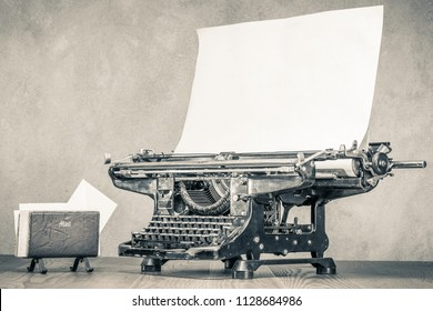 Retro aged black typewriter with large paper blank and old mail envelopes holder on wooden table front concrete wall background. Vintage style sepia photo photo
