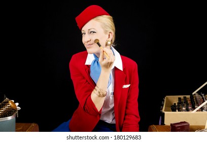 Retro Airline Stewardess or Flight Attendant Applying Make-up with a Brush at her Vanity